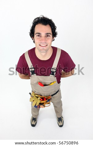 Portrait of a young worker in overalls on white background - stock photo