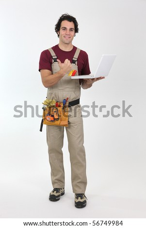 Portrait of a young worker in overalls with laptop computer on white background - stock photo