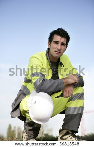 Portrait of a young worker with safety helmet crouching - stock photo