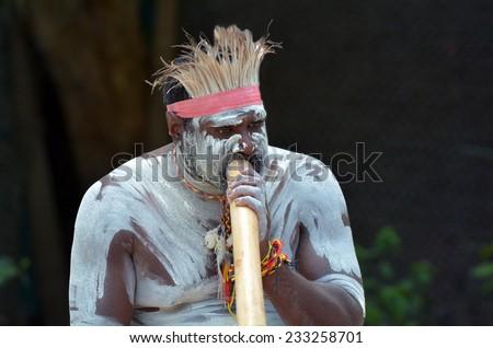 Portrait of a Yugambeh Aboriginal man play Aboriginal  music on didgeridoo, instrument during Aboriginal culture show in Queensland, Australia. - stock photo