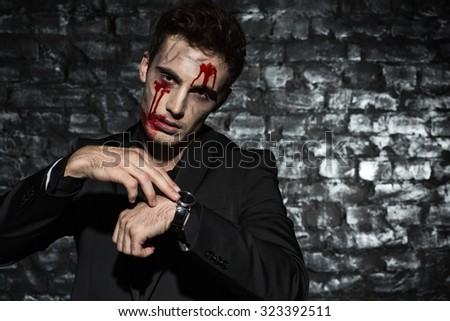 Portrait of a zombie businessman  standing and looking at his watches, wearing a black suit, with blood on his face