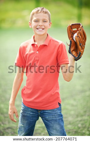 Portrait of active boy with caught baseball looking at camera in the countryside - stock photo