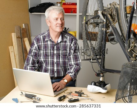 Portrait of active retired man sitting at bike repair shop while working at laptop. Small business.  - stock photo