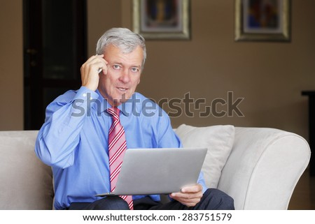 Portrait of active retired man sitting at sofa and working online.  Senior businessman using laptop and speaking on his smartphone. - stock photo