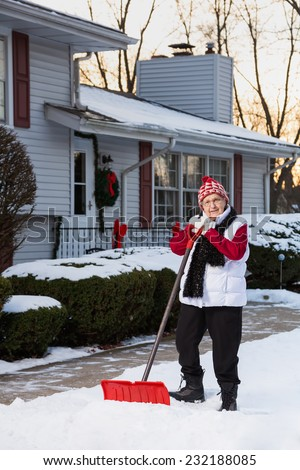 Portrait of Active Senior Citizen with Snow Shovel in Front of House (Vertical)