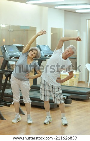 Portrait of active senior couple exercising in gym