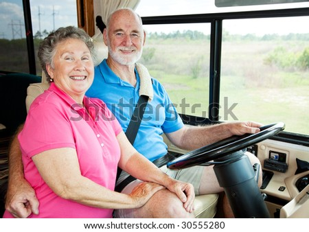 Portrait of active senior couple in their motor home. - stock photo