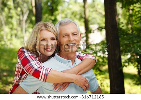 Portrait of active senior couple strolling in the forest while elderly woman arm around her husband.  - stock photo