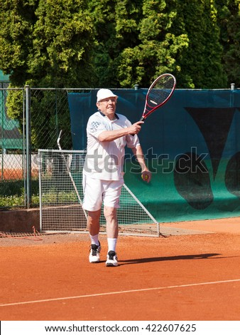 Portrait of active senior playing tennis