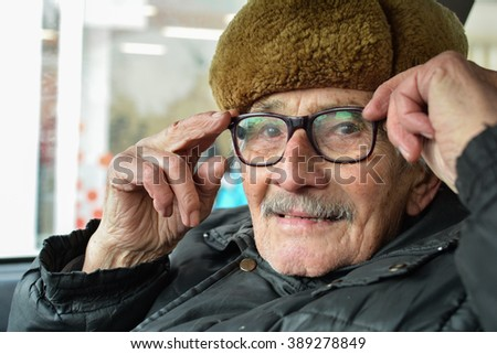 Portrait of active, vital elderly man with gray moustache and fur hat, sitting in a car and adjusting his spectacles - stock photo