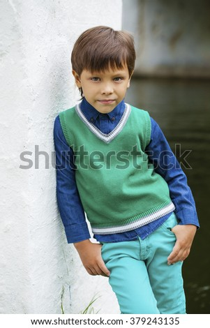 Portrait of adorable and fashionable little boy outdoor at the nice summer day