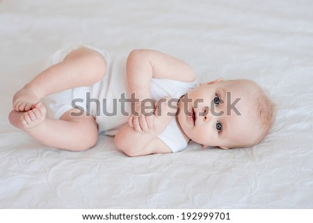 Portrait of adorable baby boy lying on the bed on his side
