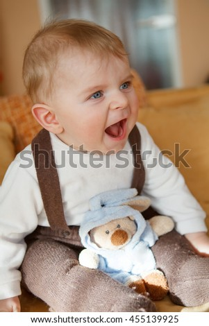 Portrait of adorable baby boy of 6 months playing with toys at home. Happy kid smiling. - stock photo