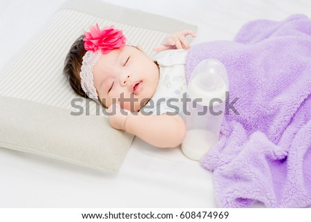 Portrait of adorable baby girl lying on the bed with milk bottle