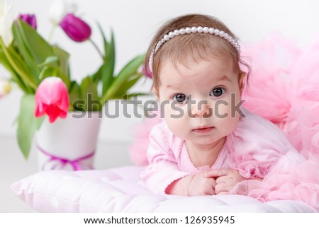 Portrait of adorable baby girl with spring flowers