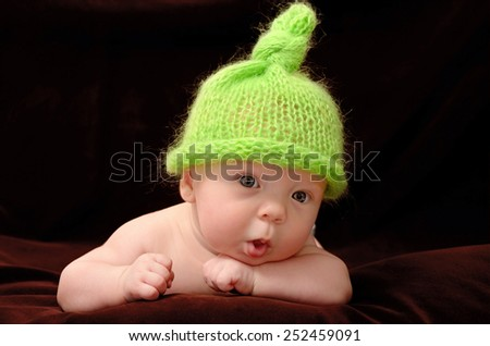 portrait of adorable baby in funny green hat looking at camera - stock photo