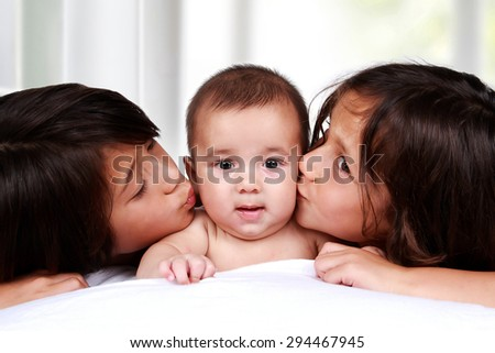 portrait of adorable baby kissed by his brothers - stock photo