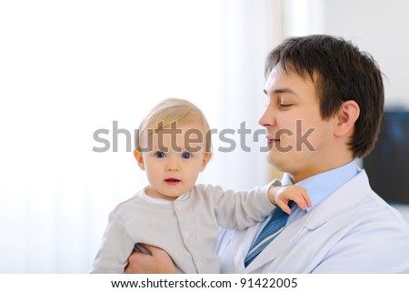 Portrait of adorable baby on hands of pediatrician