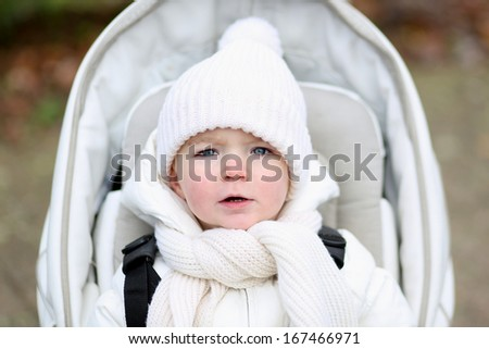 Portrait of adorable baby or toddler girl in a warm white jacket and knitted hat with scarf sitting in a stroller - stock photo