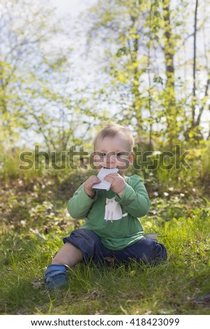 portrait of adorable blond baby toddler sitting in green grass in forest lawn, playing and eating mobile phone - stock photo