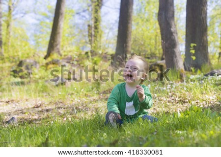 portrait of adorable blond baby toddler sitting in green grass in forest lawn, playing and laughing  - stock photo