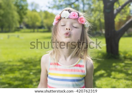 portrait of adorable blond young girl in preschool age wearing flowers in hairs and making air-kiss during traditional swedish midsummer  - stock photo