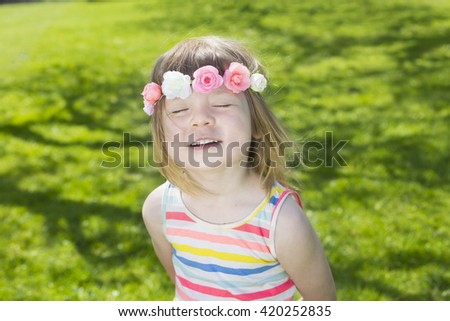 portrait of adorable blond young girl in preschool age wearing flowers in hairs outdoors enjoying sun on swedish midsummer celebration - stock photo