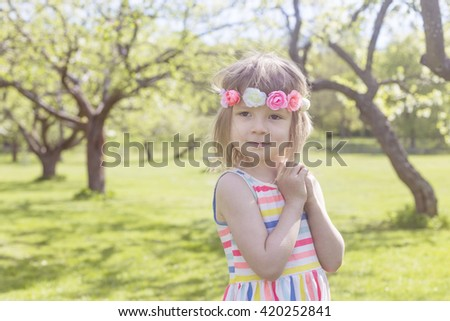 portrait of adorable blond young girl in preschool age wearing flowers in hairs outdoors enjoying soft light in apple trees park - stock photo