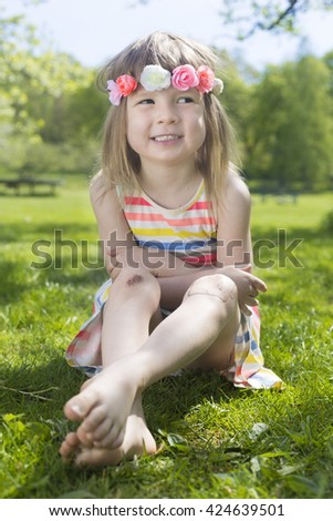 portrait of adorable blond young girl in preschool age wearing flowers in hairs outdoors, sitting on the green grass lawn - stock photo