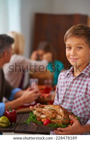 Portrait of adorable boy with roasted turkey looking at camera with smile - stock photo