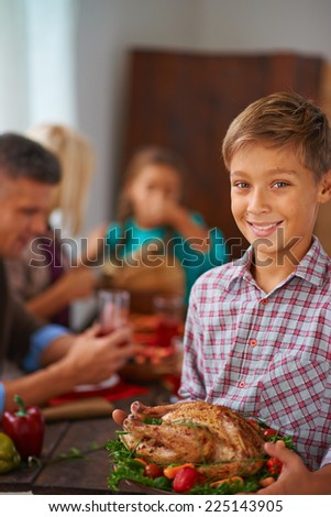 Portrait of adorable boy with roasted turkey on plate looking at camera with his family on background - stock photo