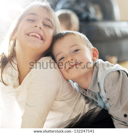 Portrait of adorable brother and sister smile and laugh together - stock photo