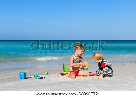 portrait of adorable cheerful blond girl in preschool age playing with her toddler brother at beach, sibling playing together