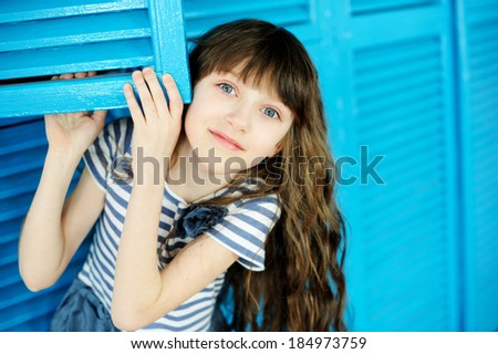 Portrait of adorable child girl on blue background - stock photo