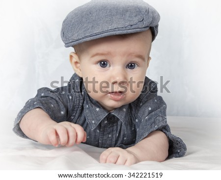Portrait of adorable child in cap lying on his tummy  - stock photo