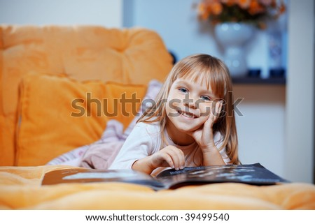 Portrait of adorable child reading magazine on sofa at home - stock photo