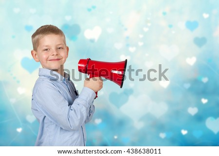 Portrait of adorable child with a megaphone over blue background - stock photo