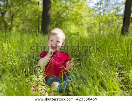 portrait of adorable cute baby toddler wearing bright red shirt sitting in fresh green grass in park or forest - stock photo