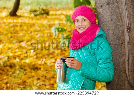 Portrait of Adorable cute girl resting and drinking tea from a thermos in the beauty autumn park