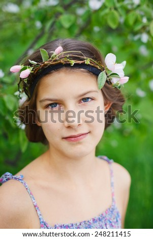 Portrait of adorable girl in blooming apple tree garden on spring day - stock photo