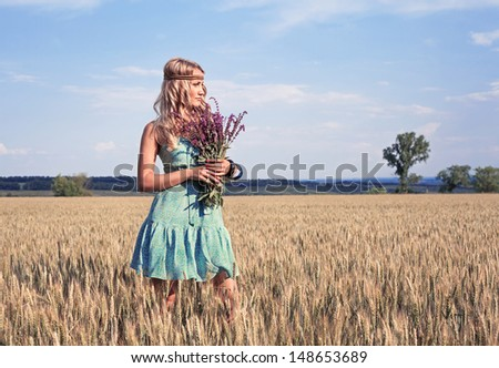 Portrait of adorable girl with wildflowers flowers poses in a field during summer afternoon - stock photo