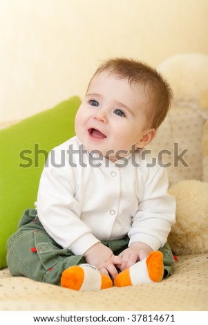 Portrait of adorable happy blue-eyes baby sitting on sofa