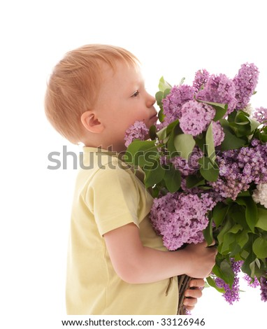 Portrait of adorable happy boy smelling big bouquet of lilac - stock photo