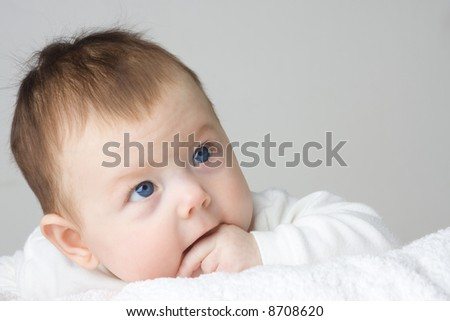 Portrait of adorable infant girl clothed in white