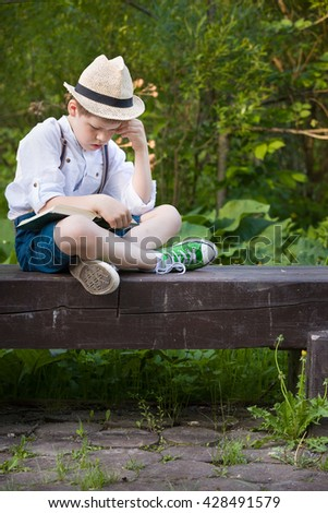 Portrait of adorable kid boy in a straw hat sitting on a wooden bench and reading book in the park. Child reading in the garden on a summer day. Outdoors. Education and leisure concept. Lifestyle. - stock photo