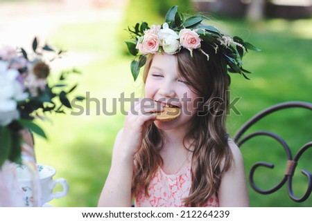 Portrait of adorable kid girl with flower wreath  and cookie outdoor in the garden  - stock photo