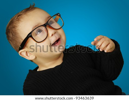 portrait of adorable kid wearing glasses and gesturing over blue background - stock photo