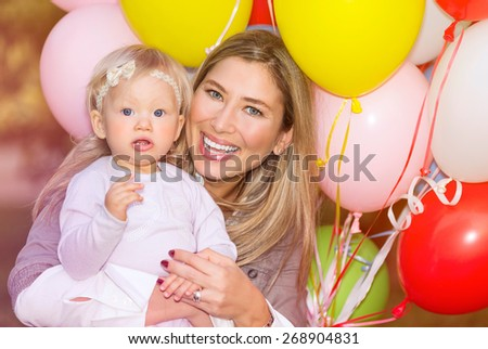 Portrait of adorable little baby girl celebrating birthday with her beautiful cheerful mother, colorful balloons decoration, happiness and pleasure concept - stock photo