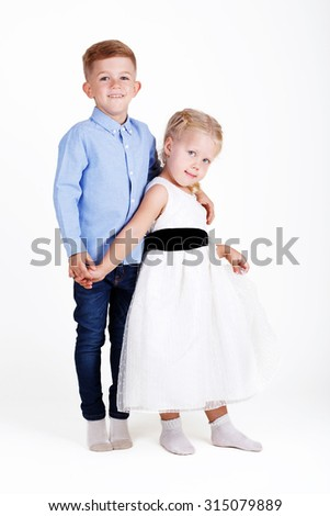 portrait of adorable little boy and girl on white background - stock photo