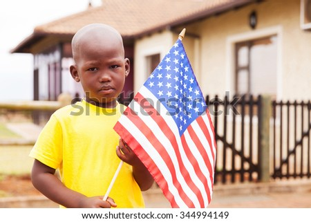portrait of adorable little boy holding american flag in front of house